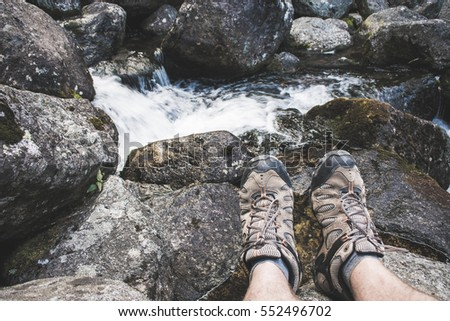 Resting by the river. First person perspective of hiking shoes.