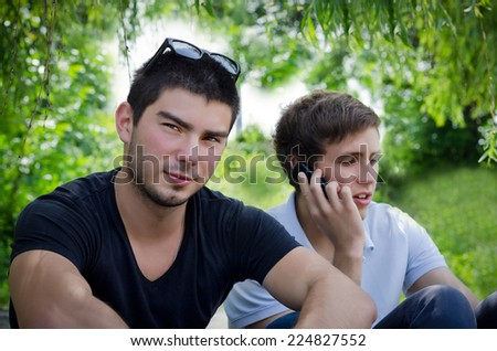 Resting in the shade two young men enjoy a respite during a long walk in lush green surroundings - stock photo