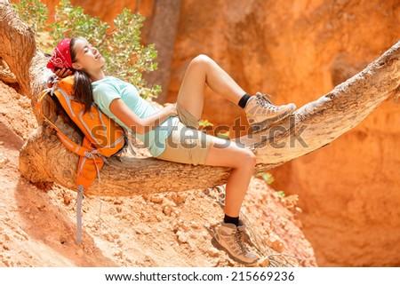 Resting relaxing woman hiker lying down enjoying the sun during hiking travel trek Bryce Canyon National Park landscape, Utah, USA. Beautiful young female hiker. - stock photo