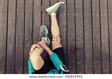 resting sportsman's legs sitting on the wooden floor with red sport plastic bottle, view from the top - stock photo