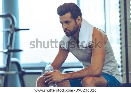 Resting time. Handsome young men in sports wear wearing towel on his shoulders and holding water bottle while sitting at gym - stock photo