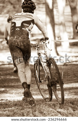 RESTON, VIRGINIA - DECEMBER 7: A cyclist is covered in mud at the Capital 'Cross Classic cyclocross competition on December 7, 2014 in Reston, Virginia - stock photo
