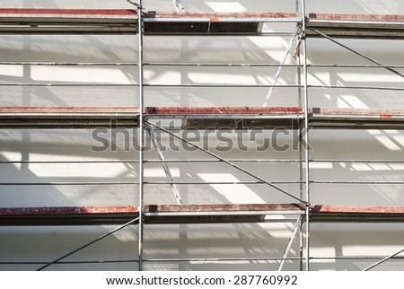 restoration facade of a house, scaffolding construction  - stock photo