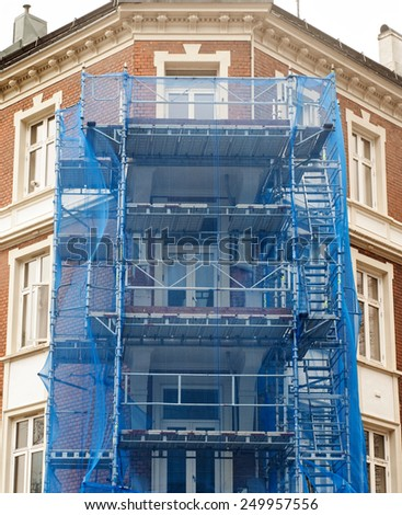 restoration facade of old house under blue net - stock photo