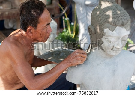 restore buddhist figure, old Asian man with his craft