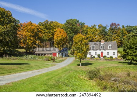 Restored cape-style New England country home with barn and wood shed surrounded by colorful Autumn foliage. Dirt driveway and mailbox. - stock photo