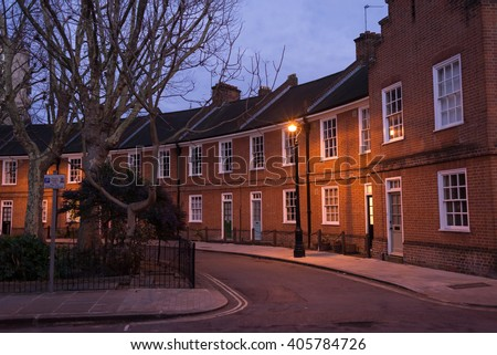 Restored Edwardian brick houses on a local road at night with street lamp - stock photo