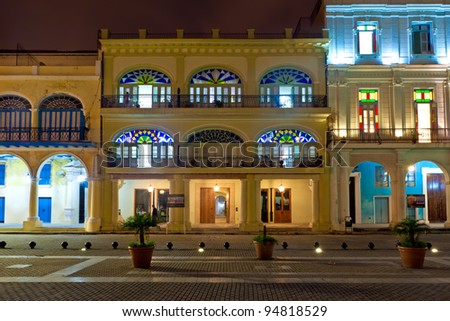 Restored historical colonial buildings in Old Havana illuminated at night - stock photo