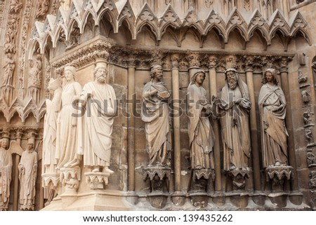 restored statues in contrast with the old ones, on the front of Cathedral of Notre-Dame, Reims, France - stock photo
