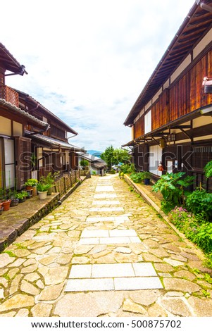 Restored traditional wooden houses line the sides of a stone walking path on the ancient Nakasendo trail during daytime in Magome, Kiso Valley, Japan. Vertical