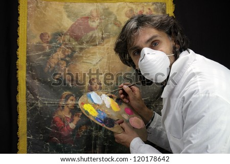 restorer at work on damaged ancient painting - stock photo