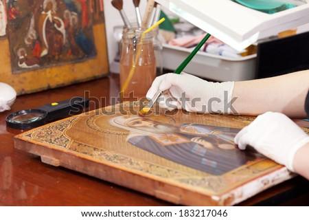 restorer works on old gilded icon with brush at restoration workshop  - stock photo