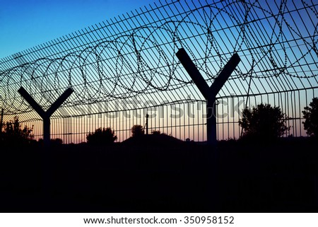 Restricted area - fence with barbed wire. - stock photo