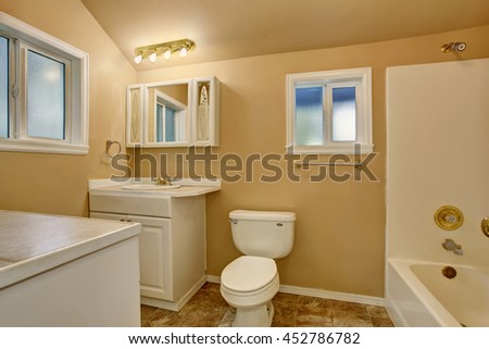 Restroom interior with beige walls. Refreshing white vanity cabinet with mirror