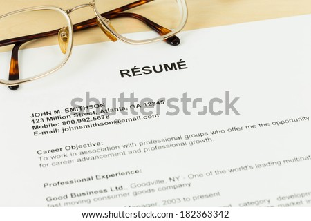 Resume and glasses on table closeup - stock photo