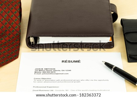 Resume, pen, neck tie, and notebook - stock photo