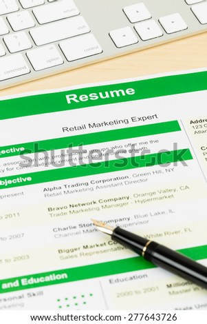 Resume with keyboard and pen; document and information are mock-up - stock photo
