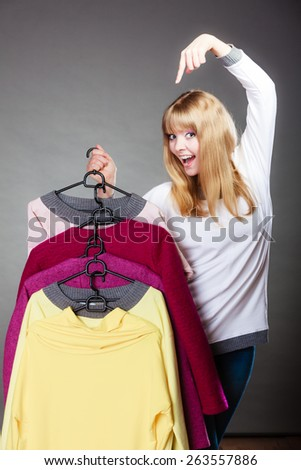Retail and sale. Blonde girl fashionable woman showing clothes. Client customer pointing with finger hangers with colorful clothing gray background - stock photo