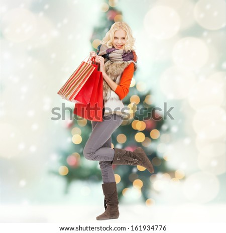 retail and sale concept - happy teenage girl in winter clothes with shopping bags - stock photo