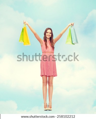 retail and sale concept - smiling woman in dress and high heels with many shopping bags - stock photo