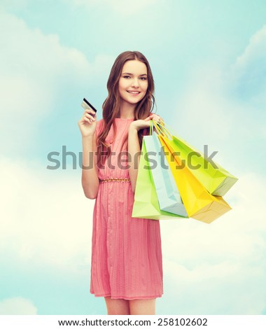 retail and sale concept - smiling woman in dress with many shopping bags and credit card - stock photo