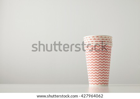 Retail set of four paper cups decorated with red lines pattern isolated on white table - stock photo
