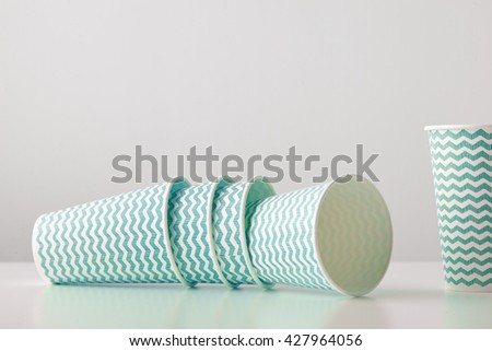 Retail set of three paper cups decorated with blue lines pattern felt down and one standing near isolated on white table - stock photo