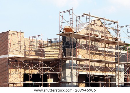 Retail shopping center under construction.  Image shows brick work and scaffolding. - stock photo