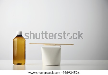 Retail takeaway presentation business set: plastic brown bottle with water on left side of closed blank noodles box with wok noodles inside and chopsticks on top isolated on white - stock photo