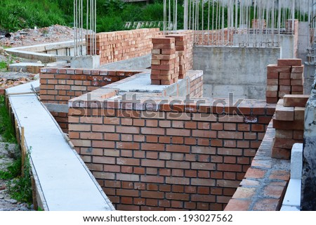 Retaining wall, red brick masonry and reinforced concrete pillars on house under construction. - stock photo