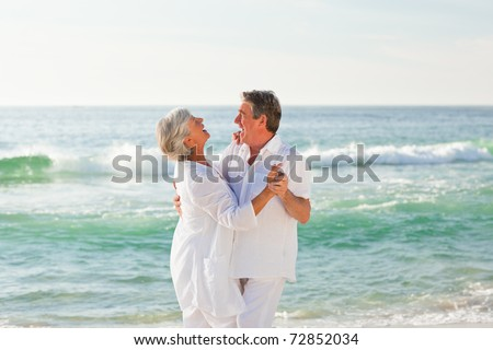Retired couple dancing on the beach - stock photo