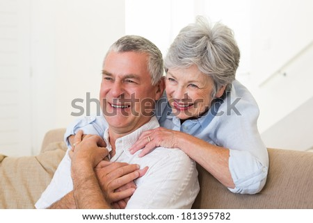 Retired couple embracing at home in living room - stock photo