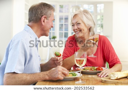 Retired couple enjoying meal at home - stock photo