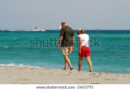 Retired couple on the beach enjoying comfortable retirement and financial freedom