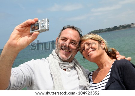 Retired couple taking picture of themselves by the sea - stock photo