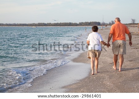 Retired couple walking hand in hand on the beach.  Rear view. - stock photo