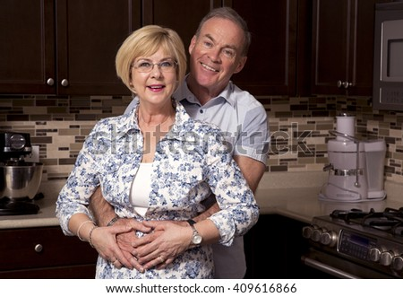 retired couple wearing casual outfits in the kitchen - stock photo