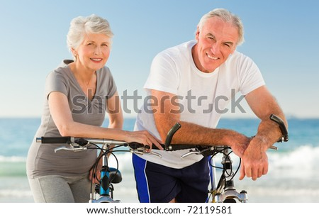 Retired couple with their bikes on the beach - stock photo