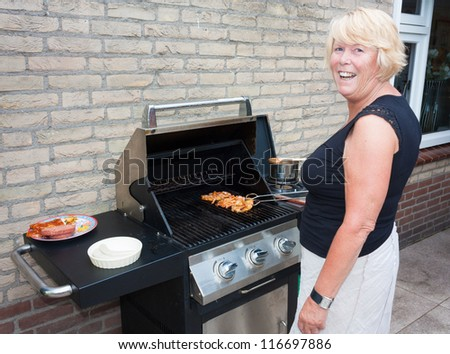 Retired dutch senior woman grilling pork chops in her back yard on a summer day - stock photo