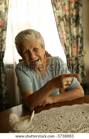 Retired elderly woman laughing and pointing at something