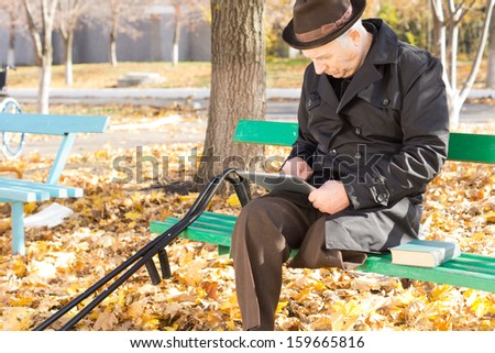 Retired handicapped man with one leg amputated sitting on a park bench in the autumn sun in an overcoat and hat using a tablet computer - stock photo