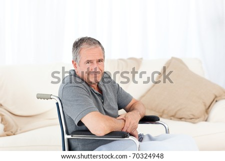 Retired man in his wheelchair at home - stock photo