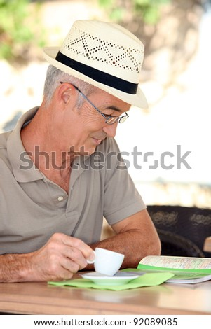 Retired man looking at a map while drinking coffee - stock photo