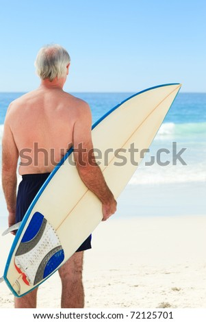 Retired  man with his surfboard - stock photo