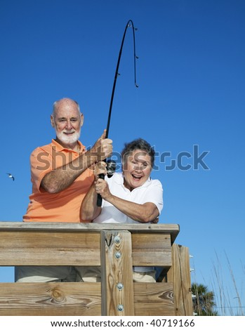 Retired senior couple reeling in a big fish on vacation.