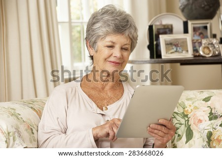 Retired Senior Woman Sitting On Sofa At Home Using Tablet Computer - stock photo