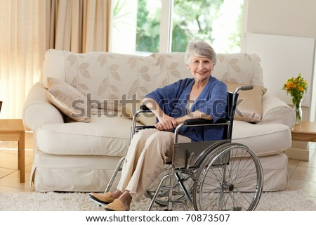 Retired woman in her wheelchair at home - stock photo