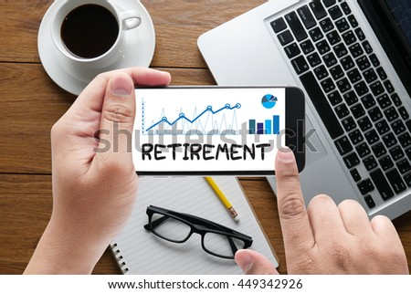 RETIREMENT message on hand holding to touch a phone, top view, table computer coffee and book - stock photo