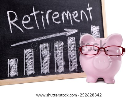 Retirement plan : Pink piggy bank with glasses standing next to a blackboard with retirement savings message.  Investment, growth, retire concept. - stock photo