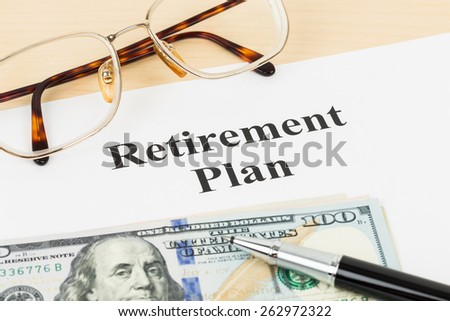Retirement plan with banknote, glasses, and pen - stock photo